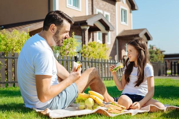 Heerlijke hapjes. aangename jonge vader en zijn schattige dochtertje zittend op het gras en sandwiches eten terwijl ze naar elkaar glimlachen