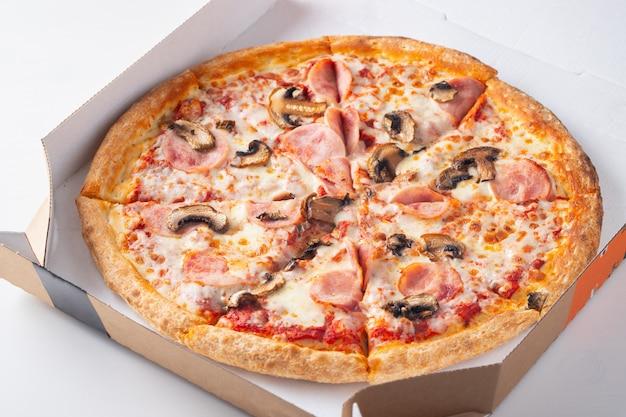 Heerlijke hete pizza in een doos met ham.