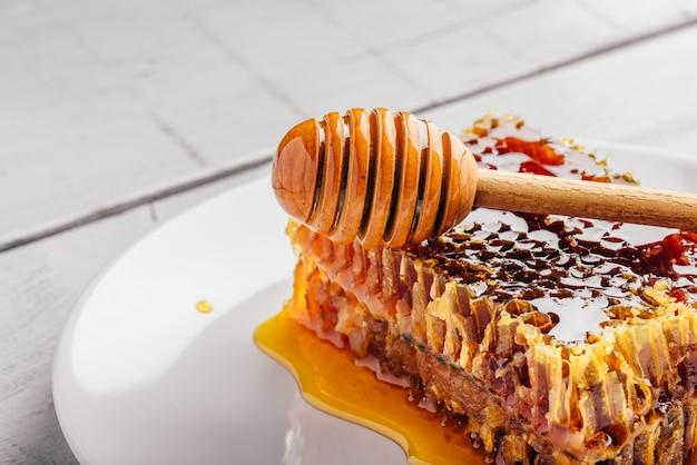 Heerlijke honingraat op witte plaat met houten honingsdipper