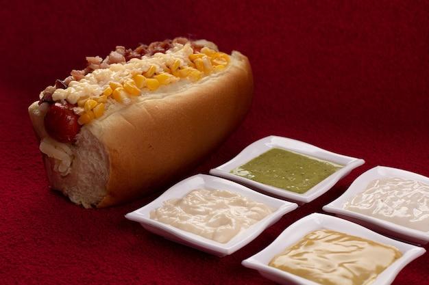 Heerlijke hotdog met ingrediënten en op kleurrijke of houten achtergrond