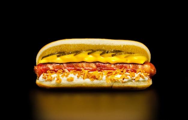 Heerlijke hotdog met worst in spek, mayonaise met uienchips, kaassaus en augurken.