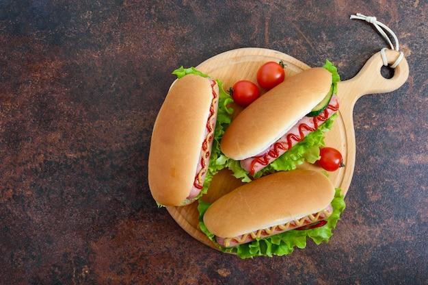 Heerlijke hotdogs met worstgrill, ketchup, mosterd, sla, tomaten op een houten dienblad. bovenaanzicht, plat gelegd.