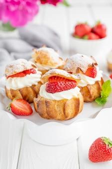 Heerlijke huisgemaakte kleine taarten soesjes soesjes met custard aardbei en glazuur poeder