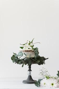 Heerlijke huwelijkscake die met bloemen tegen witte achtergrond wordt verfraaid