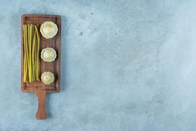 Heerlijke ingelegde minipompoen en stokjes op een bord op het marmeren oppervlak