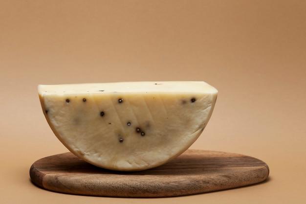 Heerlijke italiaanse kaas caciotta met geurige peperkorrels. de helft van de kaaskop op een houten bord.