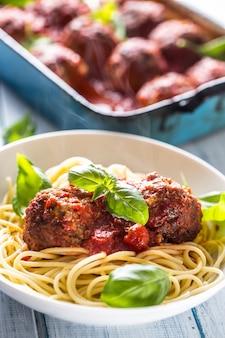 Heerlijke italiaanse maaltijd vlees rundvlees ballen met pasta spaghetti en basilicum in witte plaat.