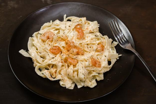 Heerlijke italiaanse pasta. fetuccini met garnalen en kruidensaus op zwarte plaat en donkere achtergrond.