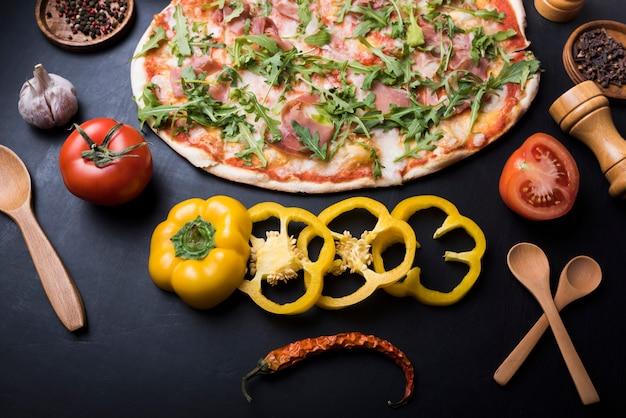 Heerlijke italiaanse pasta met verse ingrediënten en kruiden op zwarte achtergrond