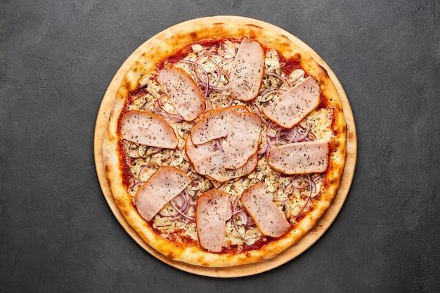 Heerlijke italiaanse pizza met ham, uien en mozzarellakaas op donkere tafel