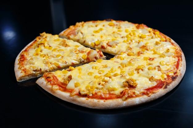 Heerlijke italiaanse pizza met rauw vlees, tomaten en olijfolie op een donkere betonnen tafel. bovenaanzicht met kopie ruimte.
