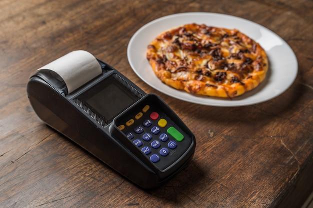 Heerlijke italiaanse pizza's geserveerd op houten tafel met betaling ter