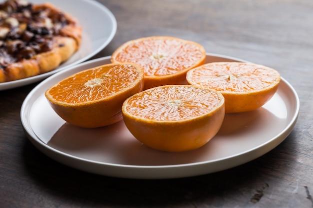 Heerlijke italiaanse pizza's geserveerd op houten tafel met oranje