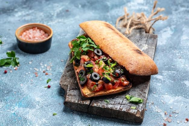 Heerlijke italiaanse tomaten bruschetta ciabatta met olijven, groenten, kruiden en olie op gegrild of geroosterd knapperig stokbrood bestrooid met kruiden.