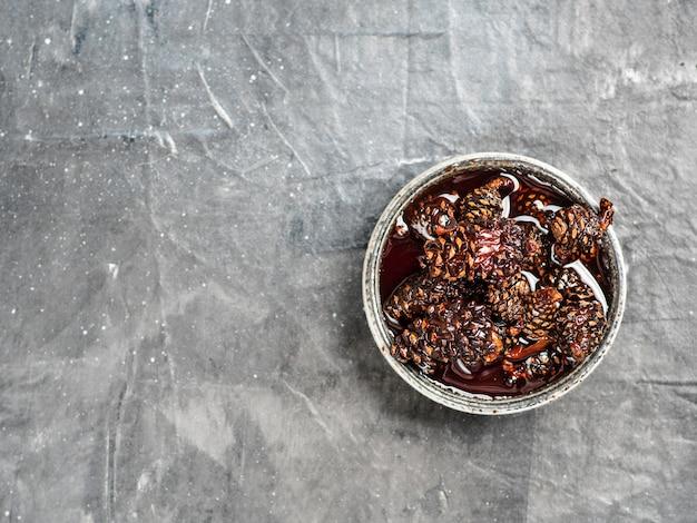 Heerlijke jam met babydenneappels in kleine kom. traditioneel siberisch dessert met jonge denneappelsjam op grijze textuur