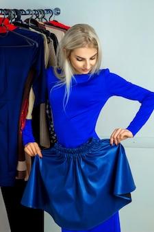 Heerlijke jonge blonde vrouw die een rok probeert