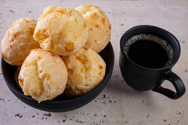 Heerlijke kaasbroodjes en een kopje koffie op wit marmer.