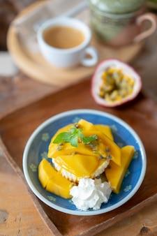 Heerlijke kaaspastei met de passievrucht en de mango op houten lijst