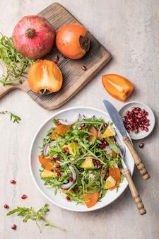 Heerlijke kaki salade met rucola en sinaasappel geserveerd op lichtgrijze tafel, plat leggen. ruimte voor tekst
