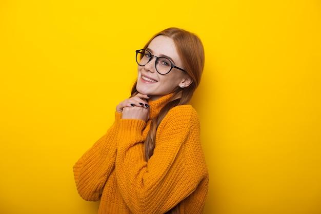 Heerlijke kaukasische dame met sproeten en rood haar die door oogglazen op een gele muur kijken