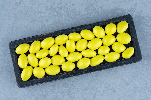 Heerlijke kauwgom in het houten dienblad, op de marmeren tafel.