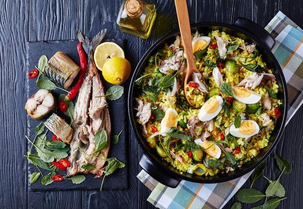 Heerlijke kedgeree met vlokken van gerookte vis, hardgekookte eieren, rijst, boerenkool, spruitjes, specerijen en kruiden in een nederlandse oven op een zwarte houten tafel met ingrediënten, uitzicht van bovenaf, flatlay