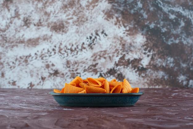 Heerlijke kegelchips in een bord, op de marmeren tafel.