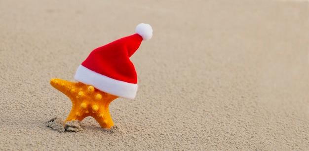 Heerlijke kerst op het strand, zeesterren in een clausmuts