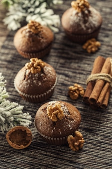 Heerlijke kerstchocolade muffins bestrooid met suikerpoeder en walnoot erop.