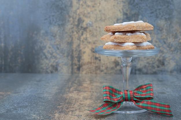 Heerlijke kerstkoekjes op glazen plaat met strik op marmeren achtergrond.