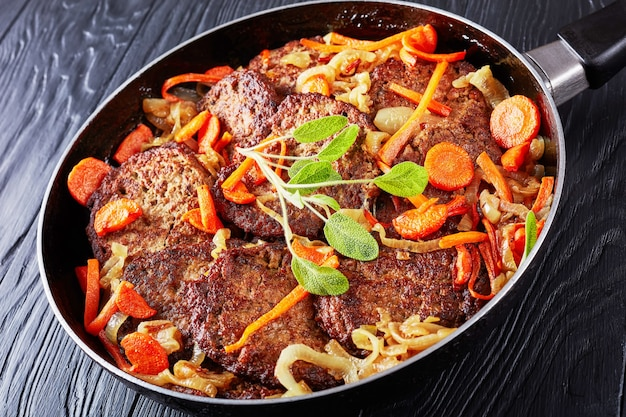 Heerlijke kippenleverpannenkoekjes gestoofd met wortel en ui in een koekenpan