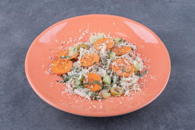 Heerlijke kippensalade op oranje plaat.