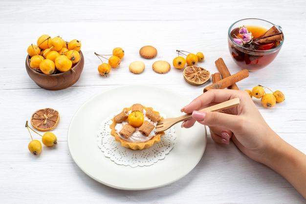Heerlijke kleine cake die door vrouw wordt gegeten, samen met gele kersen kaneelkoekjes en thee op lichtbureau, koekjescake koekje zoet