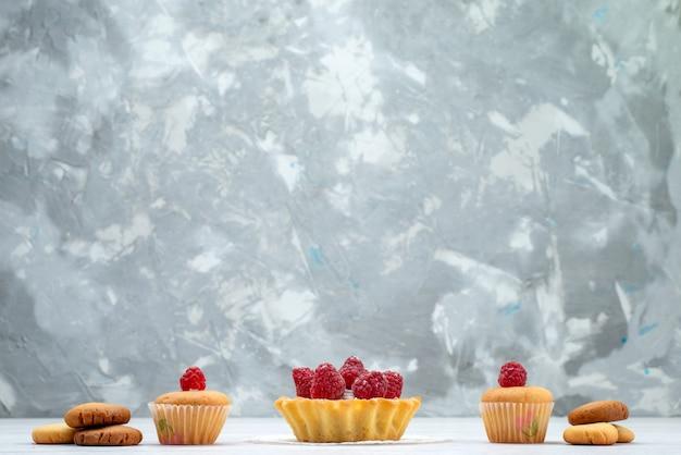Heerlijke kleine cakes met frambozen samen met koekjes op licht, cake koekje zoete bes
