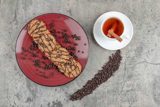 Heerlijke koekjes bestrooid met chocoladedruppels op rode plaat en kopje thee.