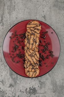 Heerlijke koekjes bestrooid met chocoladedruppels op rode plaat.