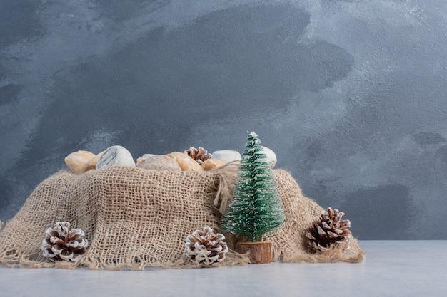 Heerlijke koekjes gebundeld op een stuk doek temidden van kerstversieringen op een marmeren oppervlak
