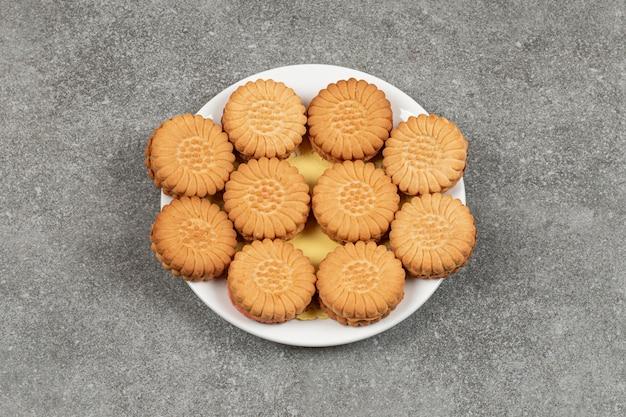 Heerlijke koekjes gevuld met room op een witte plaat