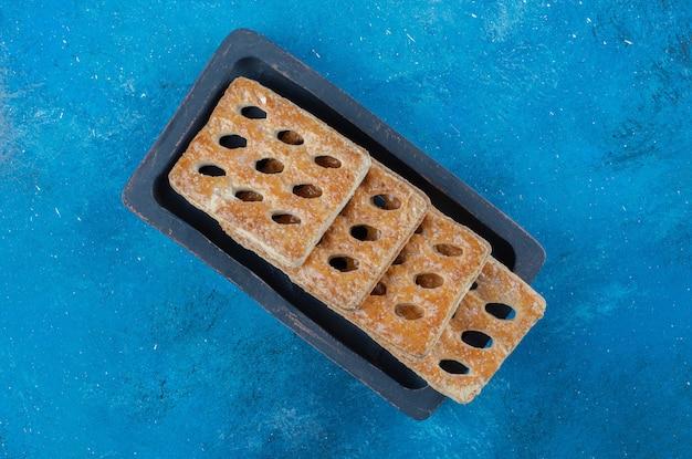 Heerlijke koekjes in de houten kist op de blauwe achtergrond. hoge kwaliteit foto
