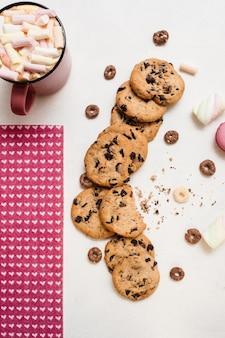 Heerlijke koekjes met chocolade en warme drank met marshmallow op witte tafel
