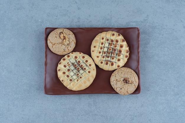 Heerlijke koekjes op bruine plaat over grijs. bovenaanzicht.