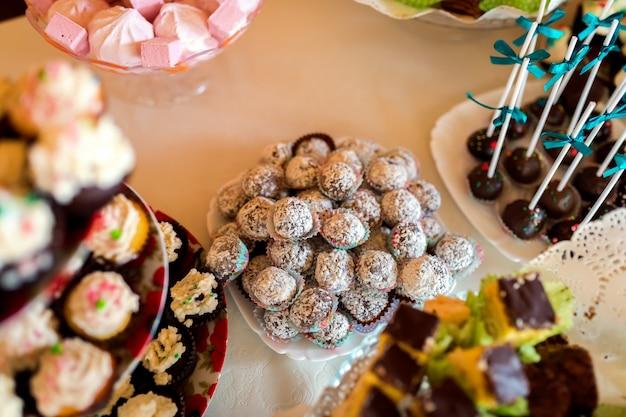 Heerlijke koekjes op de bruiloft tafel voor gasten op het witte tafelkleed.