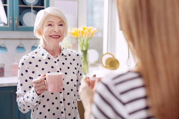Heerlijke koffie. de focus ligt op een charmante senior vrouw die in de keuken staat en samen met haar dochter koffie drinkt en met haar praat