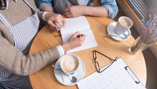 Heerlijke koffie. jong aangenaam paar café-eigenaren hand in hand en koffie drinken tijdens het werken aan de tafel.