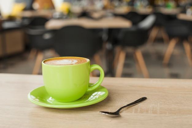 Heerlijke koffiekop met latte kunst op lijst bij restaurant