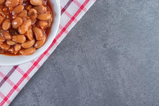 Heerlijke kom gebakken bonen op een theedoek op het blauwe oppervlak