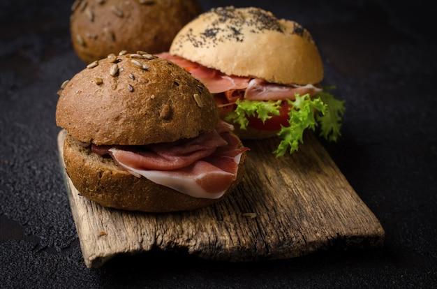 Heerlijke krokante burger bun met gesneden ham op een vintage houten snijplank. donker humeurig eten stilleven.