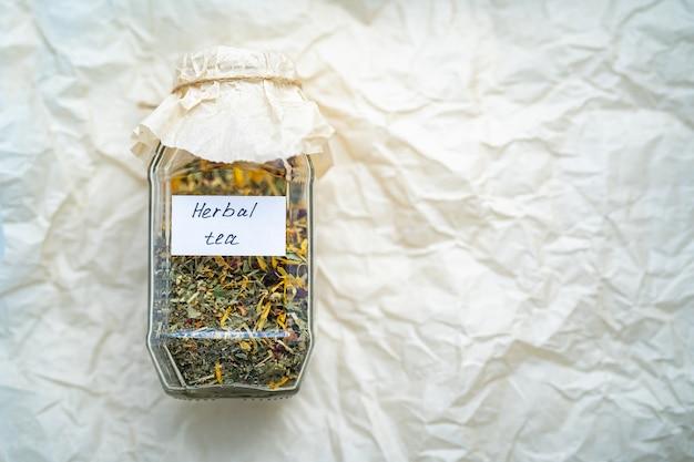 Heerlijke kruidenthee in glazen pot. droog nuttig kruid om te brouwen.