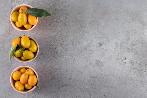 Heerlijke kumquatvruchten in kommen, op het marmeren oppervlak