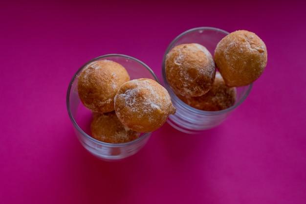 Heerlijke kwark donuts besprenkeld met poedersuiker in een glazen schaal voor desserts op een helder roze achtergrond. twee porties. het concept van zoet voedsel. donker licht. foto close-up